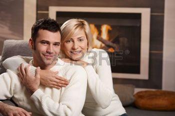 6373680-jeune-couple-longeant-sur-canap-devant-de-chemin-e--la-maison-regardant-de-cam-ra-souriant.jpg